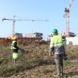Field workers with cranes in the background - Lizenzfreies Foto