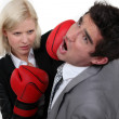 Businesswoman hitting a colleague with a boxing glove — Stock Photo #10972611