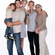 Family protected under an umbrella, studio shot — Stock Photo #10973265