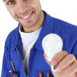 Happy electrician in jumpsuit holding bulb - Stock Photo