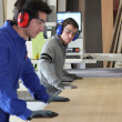Two workers using factory saw — Stockfoto