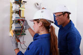 Man and woman measuring voltage — Stock Photo