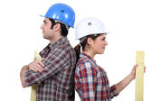 Male and female builders back to back — Stock Photo