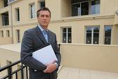 Agent nieruchomości stanął poza właściwość — Zdjęcie stockowe