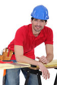 Construction worker leaning against his workbench — Stock Photo