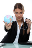 Woman holding up a mini-globe — Stock Photo