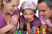 Young family playing a board game — Stock Photo