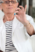 Old woman with drug in hand — Stock Photo