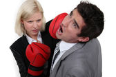 Businesswoman hitting a colleague with a boxing glove — Stock Photo