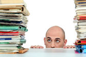 Man staring nervously at piles of folders — Stock Photo