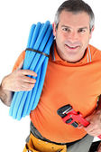 Plumber with wrench and plastic pipe — Stock Photo