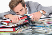 Man drowning in stacks of paperwork — Stock Photo