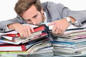 淹没在成堆的文书工作中的男人 — 图库照片