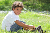 Child sitting in a field — Stock Photo
