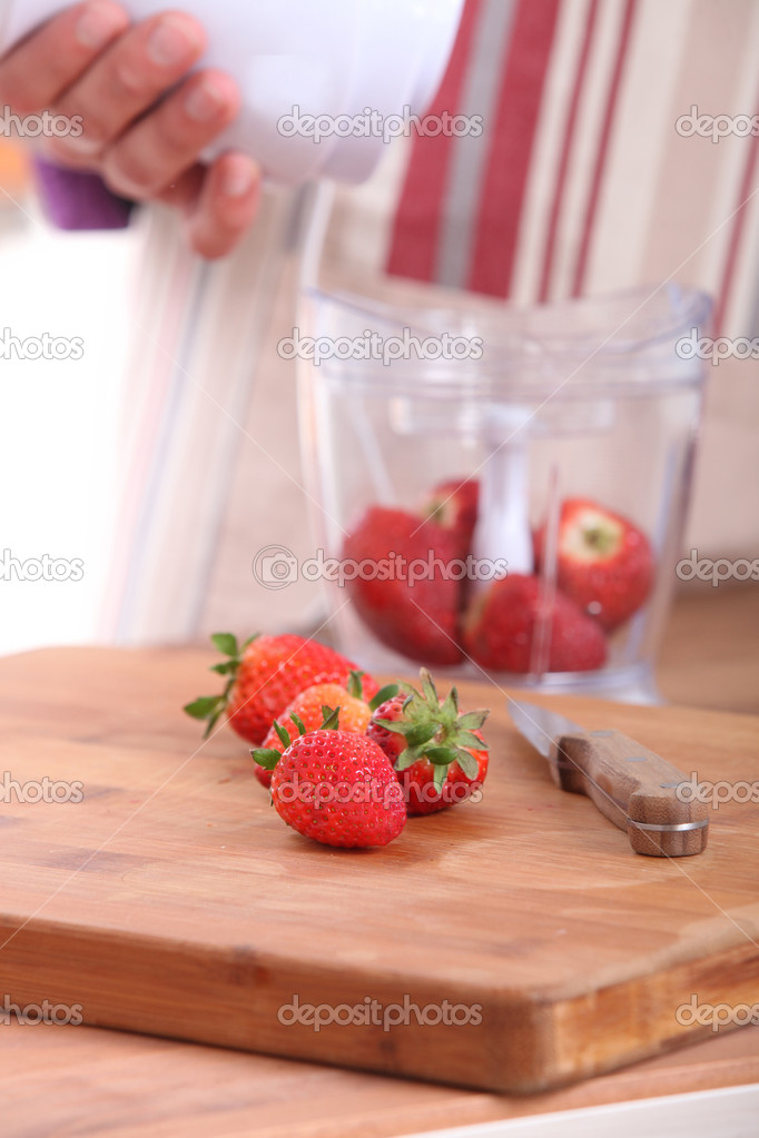 Woman putting strawberries in a blender — Stock Photo #10972466