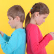 Brother and sister with hand-held video games — Stock Photo