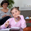 Stock Photo: Little girl doing her homework whilst her mom is sewing