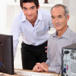 Stock Photo: Young teaching computing to senior