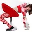 Young woman in red and white striped clothes trying to reach a jar full with bonbons — Stock Photo