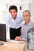 Young teaching computing to senior — Stockfoto