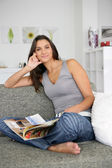 Woman sat at home reading magazine on couch — Stock Photo