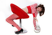 Young woman in red and white striped clothes trying to reach a jar full with bonbons — ストック写真