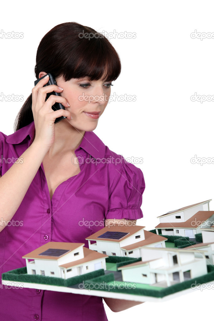 Architect holding a small-scale model while talking on the phone  Stock Photo #11016781