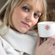 Foto Stock: Womdrinking hot beverage to warm herself up