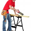 Carpenter sawing a piece of wood — Stock Photo