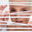 Young woman looking through the blinds - Stock Photo