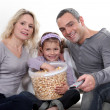 Family eating popcorn on a sofa — Stock Photo #11025548