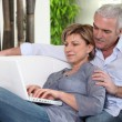 Senior couple embracing on the couch — Stock Photo
