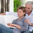 Senior couple embracing on the couch - Stock Photo