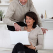 Couple with laptop computer at home — Stock Photo
