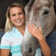 Blonde girl stroking horse — Stockfoto #11026570
