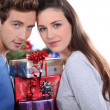 Young couple stood with pile of presents — Stock Photo #11026701