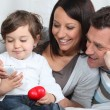 Stock Photo: Toddler holding mobile telephone whilst sat with parents on sofa