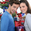Excited young couple stood by the Christmas tree — Stock Photo #11027623