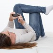 Girl laying on back watching film on her mobile — Stock Photo #11028784