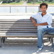 Foto Stock: Young msitting on public bench