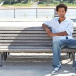 Foto de Stock  : Young msitting on public bench