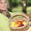 Stock Photo: Woman carrying basket of apples