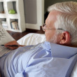 Grey-haired man completing crossword puzzle - Stock Photo