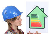 Female housebuilder with an energy rating sign — Stock Photo