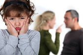 Little girl upset by parents arguing — Stock Photo