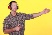 Man wearing earmuffs presenting an invisible object — Stock Photo