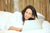 Woman with a laptop on her bed — Stockfoto