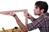 Joiner inspecting wooden frame — Stock Photo