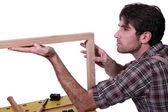 Joiner inspecting wooden frame — Stock Photo