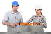 Craftsman and craftswoman erecting a wall — Stock Photo